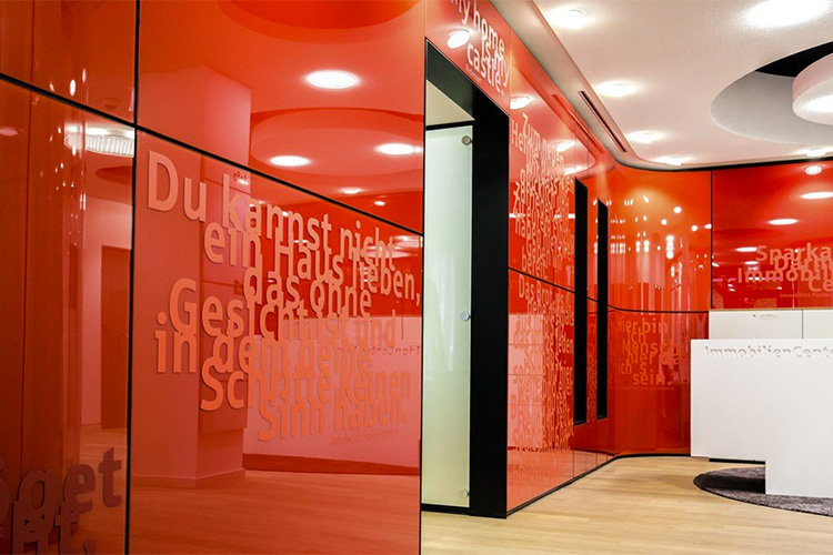 A material shows emotion: StoVentec Glass screen printed and used in the interior of a building guarantees a continuous material flow from exterior to interior. Shown is Sparkasse Darmstadt ImmobilienCenter in Germany.